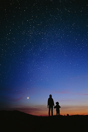 Starry sky and stargazers. Silhouetted mother and her child looking up at the starry night sky, the moon is at lower left. Photographed in British Columbia, Canada.