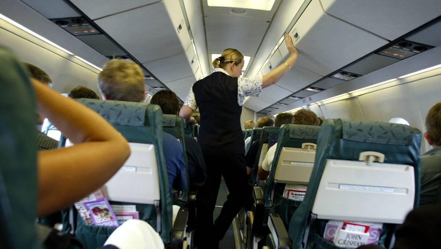 flight attendant checks overhead compartment