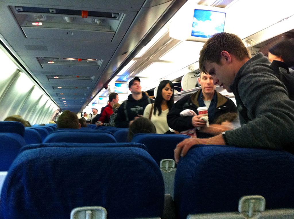 man talks to passenger on flight