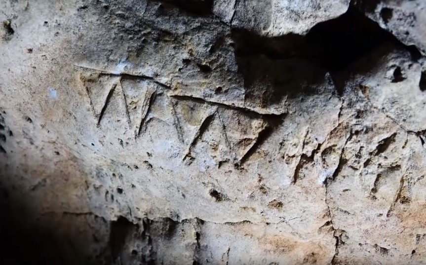 'V V' etched into the cave walls
